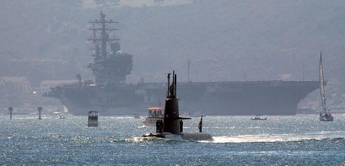 Миниатюрная шведская дизель-стирлинг-электрическая подводная лодка «Gotland» на фоне побеждённого авианосца «Рональд Рейган» класса «Нимиц»