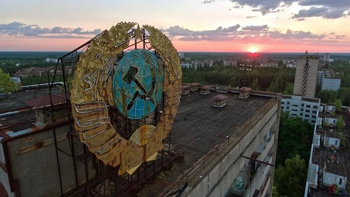 Герб СССР над малиновым закатом в Чернобыльской зоне. Фото: classpic.ru