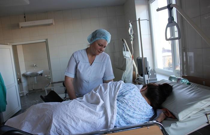 Дежурная акушерка Светлана Фролова в родильном блоке оказывает помощь матери при кормлении ребёнка.